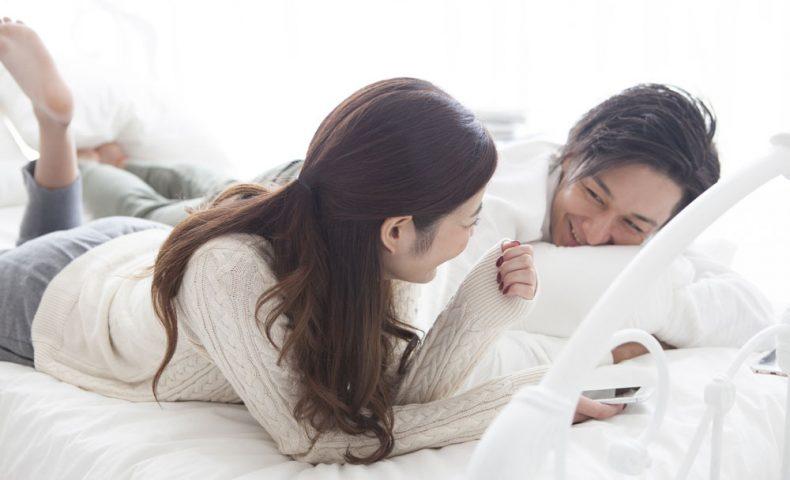 ベッドで談笑するカップル