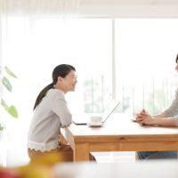 テーブルをはさんで会話する男女
