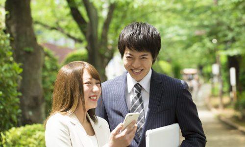 同僚の男性と親しげに会話する女性